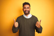 Young indian man wearing green sweater and shirt standing over isolated yellow background success sign doing positive gesture with hand, thumbs up smiling and happy. Cheerful expression