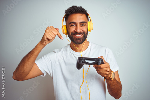 Arab indian gamer man playing video game using headphones over isolated white ba Canvas Print