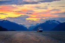 Cruise Ship With The Mountains On The Background. Vibrant Sky Colors.