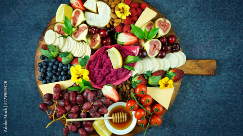 Cheese and fruit charcuterie dessert grazing platter on wooden board overhead Canvas Print