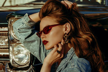 Outdoor Close Up Fashion Portrait Of Young Beautiful Fashionable Woman With Long Luxury Hair, Wearing Red Cat Eye Sunglasses, Denim Jacket, Leopard Print Earrings, Posing Near Retro Car, At The Sunset