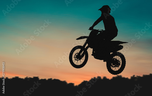 Valokuva  Motocross Dirt Bike rider getting air off of jump at sunset