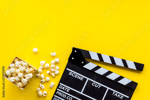 Fotografia, Obraz Watch film in cinema with popcorn and clapperboard on yellow background top view