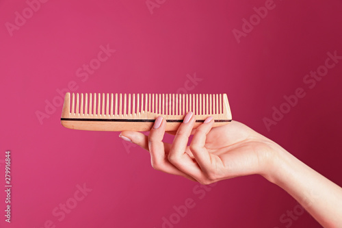 Photographie Woman holding wooden hair comb against crimson background, closeup