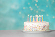 Birthday cake with burning candles on table against light blue background. Space for text