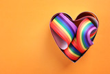Fototapeta Rainbow - Heart shaped mold and bright rainbow ribbon on color background, top view with space for text. Symbol of gay community