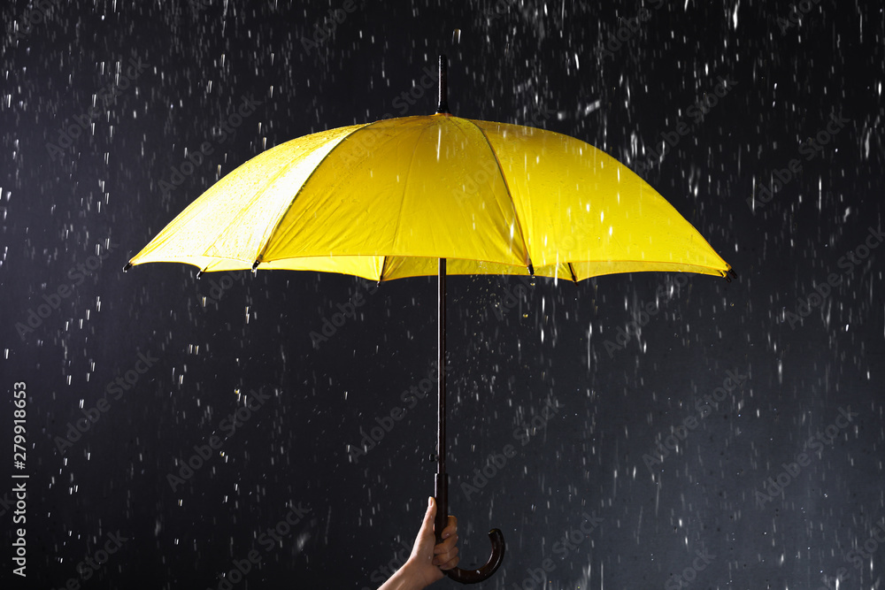 Fototapety, obrazy: Woman holding bright umbrella under rain on dark background, closeup