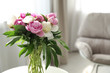 Vase with bouquet of beautiful peonies in room, space for text