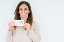 Middle Age Woman Holding 10 Pounds Bank Note Over Isolated Background With A Happy Face Standing And Smiling With A Confident Smile Showing Teeth