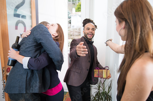Fototapeta  Group of friends greeting each other at door of home