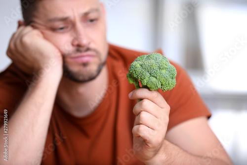 Unhappy man with broccoli on light background, closeup Fototapet