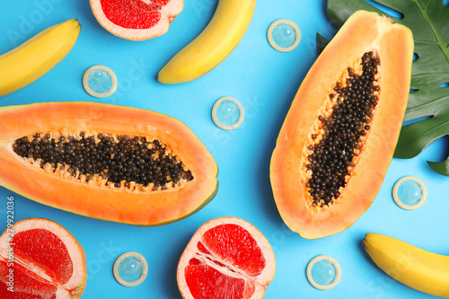 Leinwand Poster Flat lay composition with condoms and exotic fruits on blue background