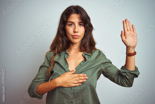Young beautiful woman wearing green shirt standing over grey isolated background Canvas Print