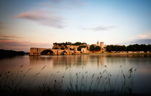 View Of Palais Des Papes By Lake At Dusk