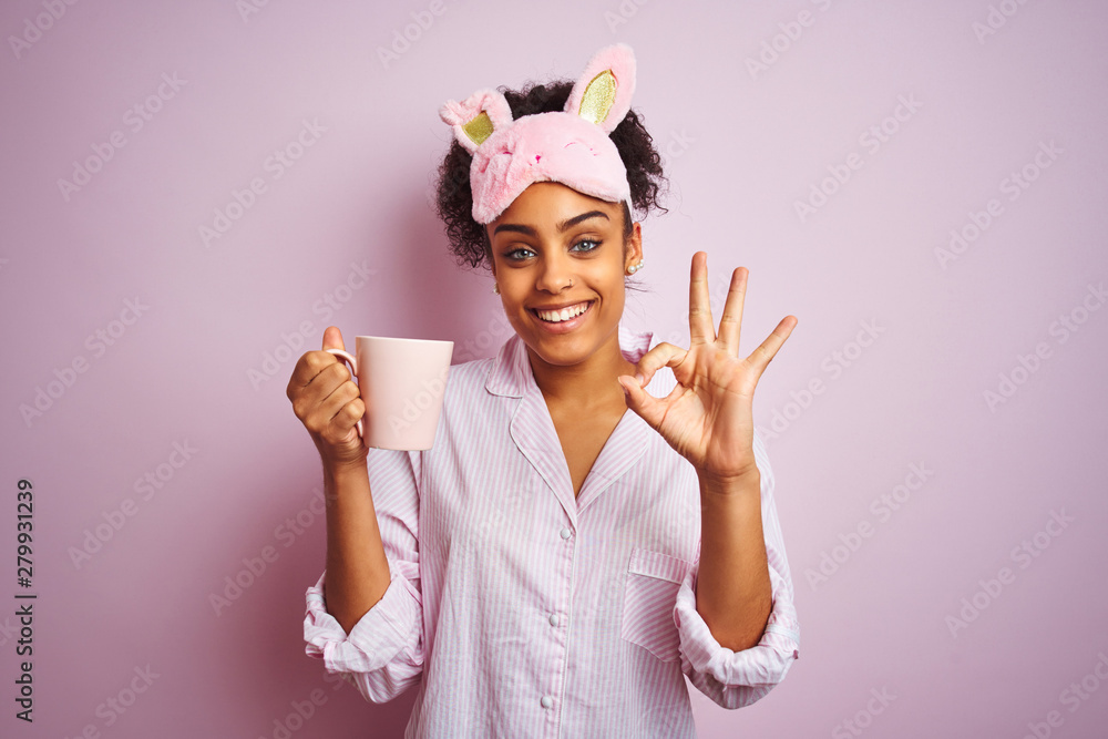 Fototapety, obrazy: Afro woman wearing pajama and mask drinking a cup of coffee over isolated pink background doing ok sign with fingers, excellent symbol