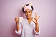 Afro woman wearing pajama and mask drinking a cup of coffee over isolated pink background doing ok sign with fingers, excellent symbol
