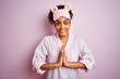 Young african american woman wearing pajama and mask over isolated pink background praying with hands together asking for forgiveness smiling confident.