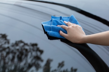 hand cleaning car using microfiber cloth