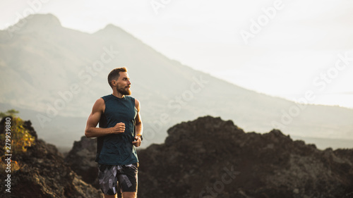 Poster Gris traffic Young athlete man trail running in mountains in the morning. Healthy lifestyle concept. Panoramic photo with empty copy space.