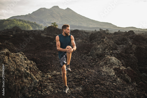 Young hipster runner with beard stretching and warming-up for trail running outdoors Canvas