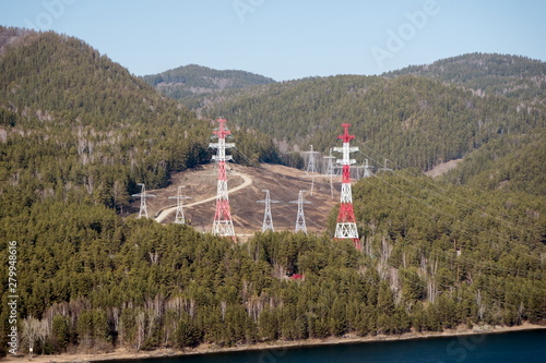 Metallic supports of overhead power lines for electricity among the Siberian forest, on the river Bank Canvas Print