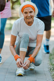 selective focus of cheerful senior woman sitting and tying shoelaces in park