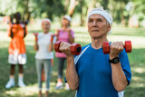 selective focus of senior man with grey hair holding dumbbells in park