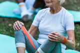 cropped view of senior woman in sportswear sitting on fitness mat