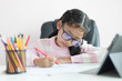 Little Asian girl using the pencil to write on the paper doing homework and smile with happiness for education concept select focus shallow depth of field