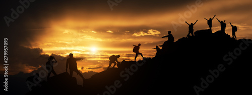 Silhouette of Hikers climbing up mountain cliff Wallpaper Mural
