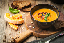 Pumpkin And Carrot Soup With Cream And Basil In Black Plate Over Wooden Background