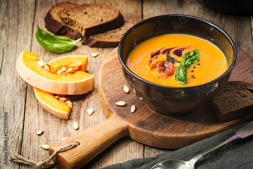 Leinwand Poster Pumpkin and carrot soup with cream and basil in black plate over wooden backgrou