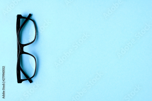 Fotografía  Black glasses on blue background composition, eyeglasses.