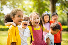 Multi-ethnic Group Of School Children Laughing And Embracing