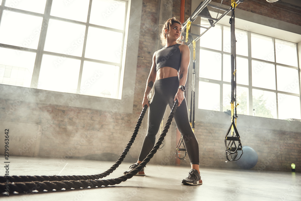 Fototapeta CrossFit training. Young athletic woman with perfect body doing crossfit exercises with a rope in the gym.