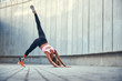Leinwanddruck Bild - Balance and flexibility. Full-length of young disabled woman with leg prosthesis in sportswear doing yoga asana outdoors. Disabled sport concept