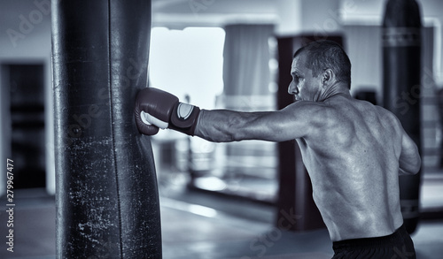 Muay thai fighter working with heavy bag Wallpaper Mural
