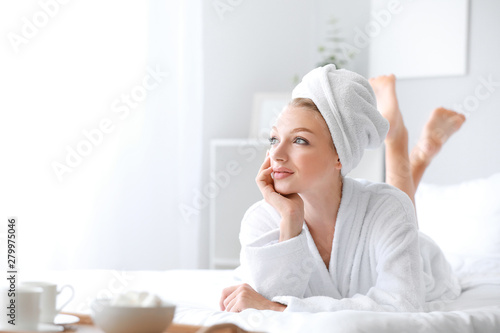 Morning of young woman in bathrobe lying on bed