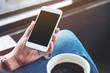 Leinwandbild Motiv Mockup image of woman holding white mobile phone with blank desktop screen while drinking coffee in cafe