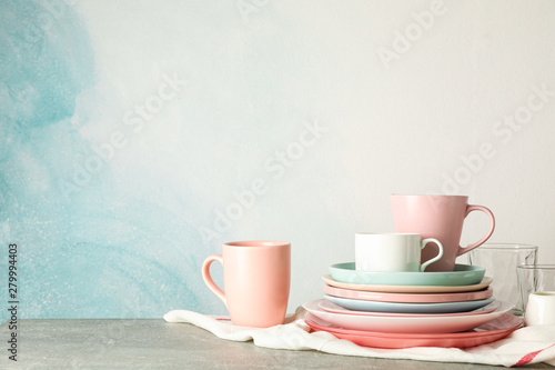 Fototapeta Color plates and cups stacked on grey table, space for text obraz na płótnie