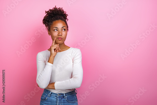 Valokuva  Studio portrait of a thinking pose girl touching herself face by index finger- I