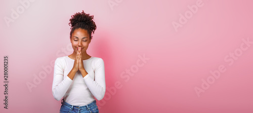 Photo  Portrait of woman in supplication pose with smile and close eyes over pink background