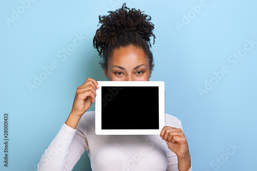 Obraz Mockup image of black empty blank screen of tablet in the female hand, peeking from behind tablet over blue background - fototapety do salonu
