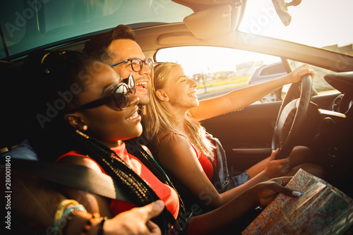 Three best friends enjoying traveling at vacation in the car.