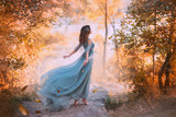 delightful light girl in sky blue turquoise dress with long flying train, princess of wind and daughter of storm, lady with dark hair throws fallen leaves to ground, autumn story in art processing.