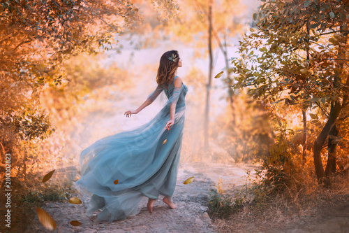 Obraz delightful light girl in sky blue turquoise dress with long flying train, princess of wind and daughter of storm, lady with dark hair throws fallen leaves to ground, autumn story in art processing. - fototapety do salonu