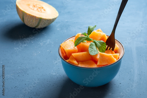 Fotografia Fresh melon cut into pieces in a bowl and background blue - image