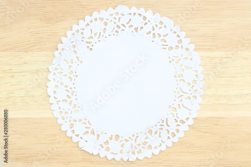 Valokuvatapetti Close up isolated white stencil doily paper like flower on wood table