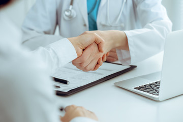 Doctor and patient shaking hands, close-up. Medicine, healthcare and trust concept