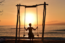 Silhouette Of The Young Woman On The Swing Watching The Sunrise In Gili Meno Island, Indonesia